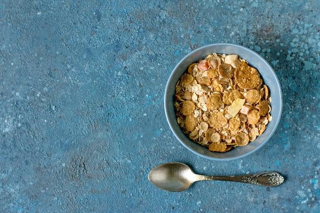 銀のテーブルスプーンとオートミールシリアル朝食のボウル