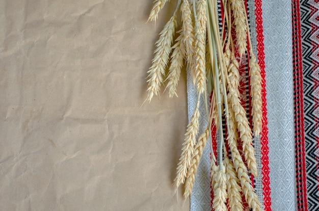 民俗刺繍布と包装パッケージ茶色の紙の熟したライ麦の穂