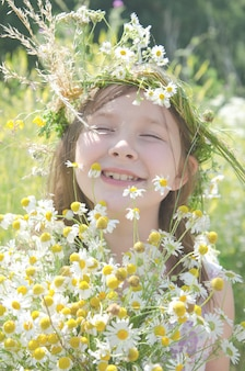 Маленькая счастливая девушка в гирлянду полевых цветов на лугу