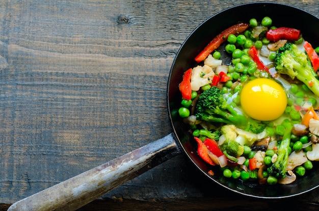 目玉焼きと野菜の混合物が入ったフライパン