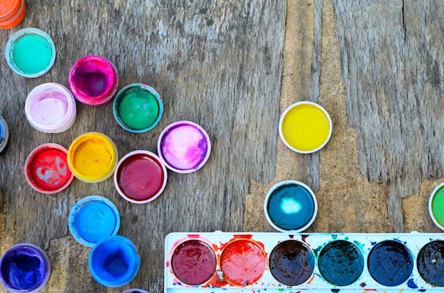 ガッシュ塗料と図面、古い木製の背景に芸術的なツールの水彩画のセット。