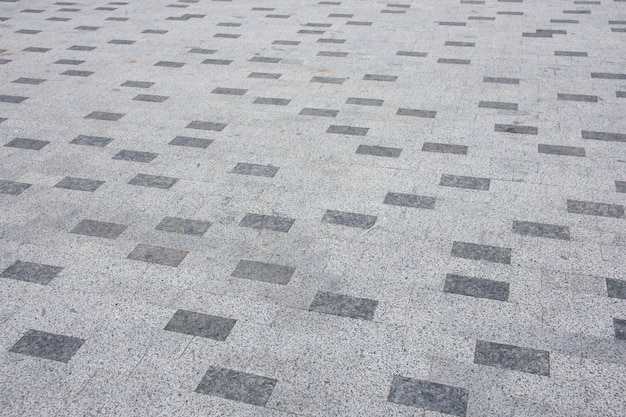 Серый кирпичный тротуар в городе по диагонали