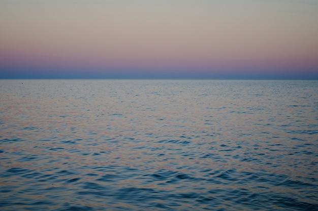 日没、青とピンクの色の後の水と地平線の海景