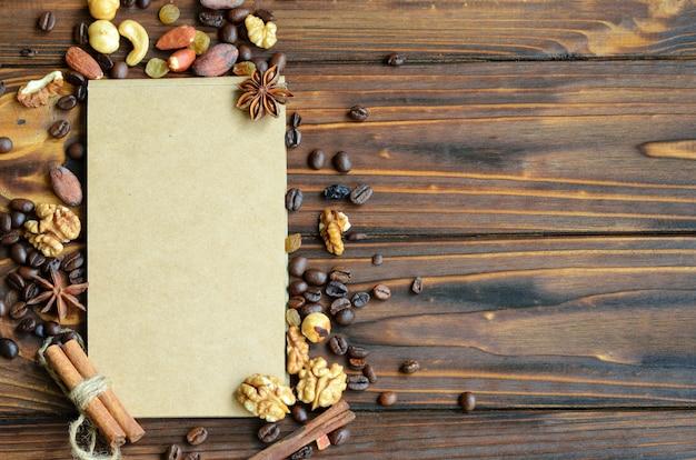 コーヒー豆、レーズン、ナッツのフレームに囲まれたペーパークラフトのメモ帳