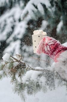 冬の雪の背景にコーヒーマシュマロとカップを保持しているピンクの手作り指なし手袋で女の子の手。冬とクリスマスの時間。