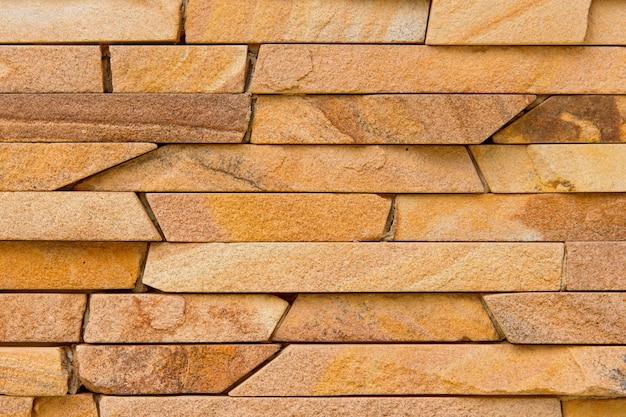 背景の欠けた石の装飾的なモダンな石の壁