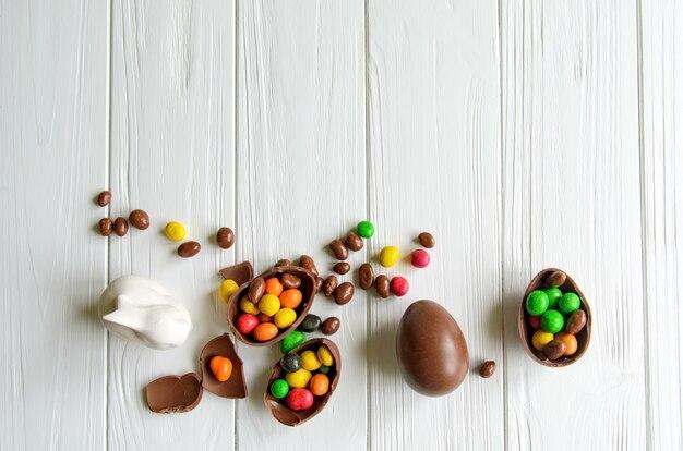 Белый пасхальный кролик с шоколадными яйцами и конфетами на белом деревянном столе