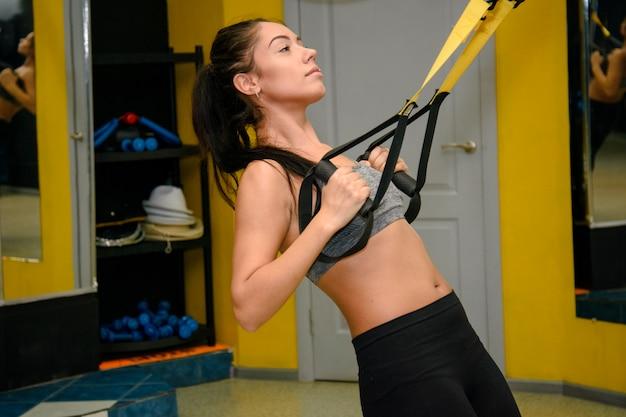 Спортсменка занимается фитнесом с фитнес-ремнями в тренажерном зале
