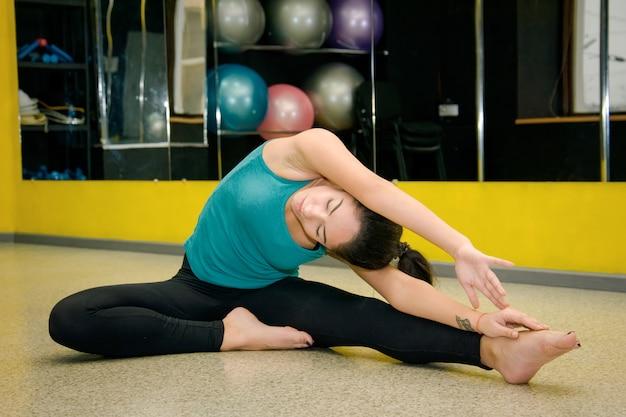 Спортсменка делает упражнения на растяжку