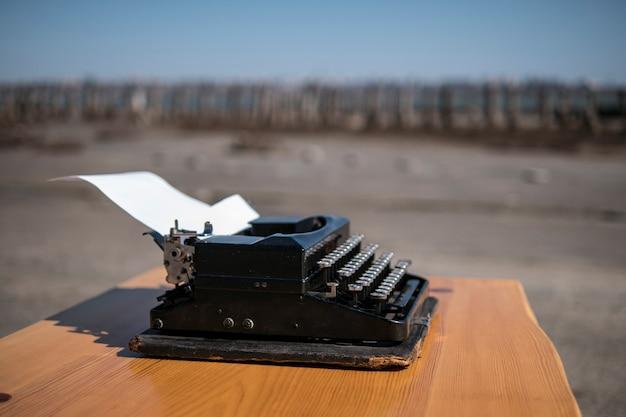 オープンエアのテーブルの上のタイプライター、背景の河口