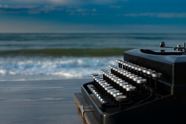 夜明けに海の背景にタイプライター。夏のビーチ