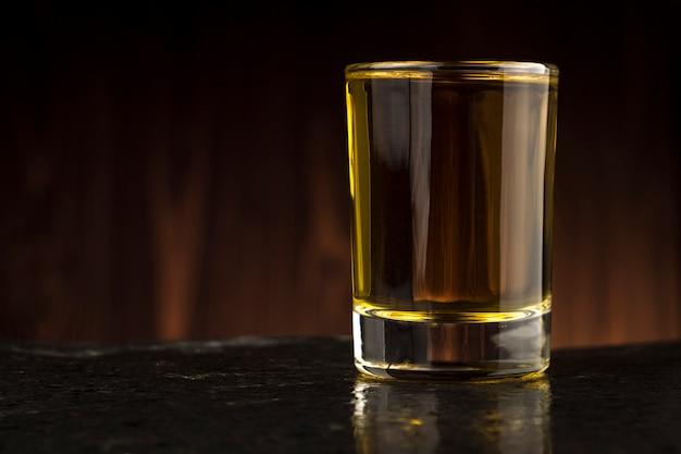 Стакан виски на столе на деревянном фоне