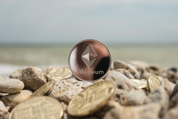 イーサクリプト通貨。電子通貨夏のビーチ。海の石