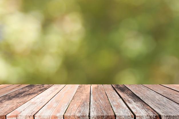 葉の背景のボケ味を持つ空の木製デッキテーブル。商品展示モンタージュの準備ができて