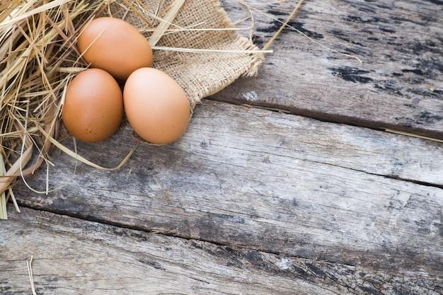 わらと古い木材の背景と麻の袋に卵