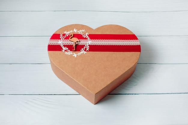 木材の背景にハート形のギフトボックス。上面図。幸せなバレンタインデー。