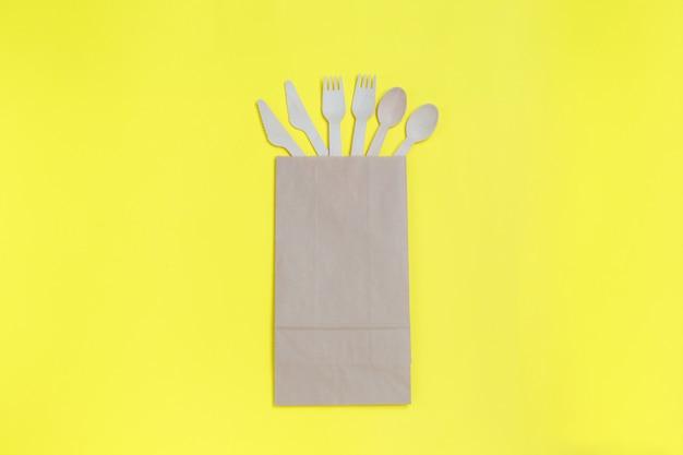 黄色の紙袋に入った天然素材、木製スプーン、ナイフ、フォークの使い捨て食器