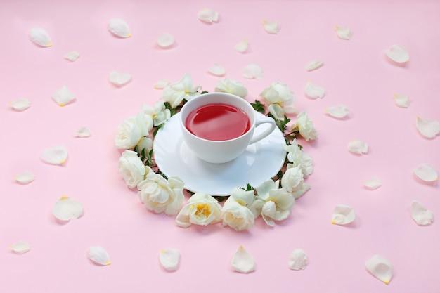 一杯のお茶と白いバラ