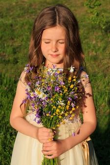 野生の花と目を閉じて花束を持つ少女