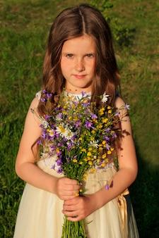 Маленькая девочка с букетом полевых цветов