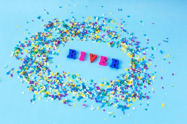 単語の川は小さなプラスチック片に囲まれています