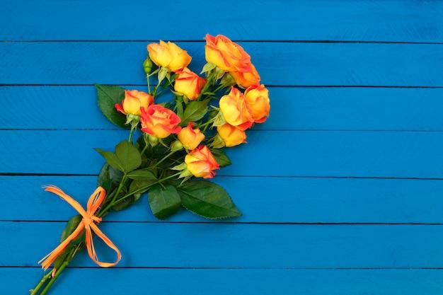 青い木製のオレンジ色のバラの花束