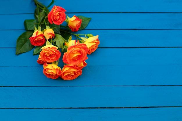 青にオレンジ色のバラの花束