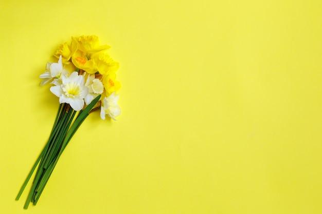 黄色の背景に水仙の花束