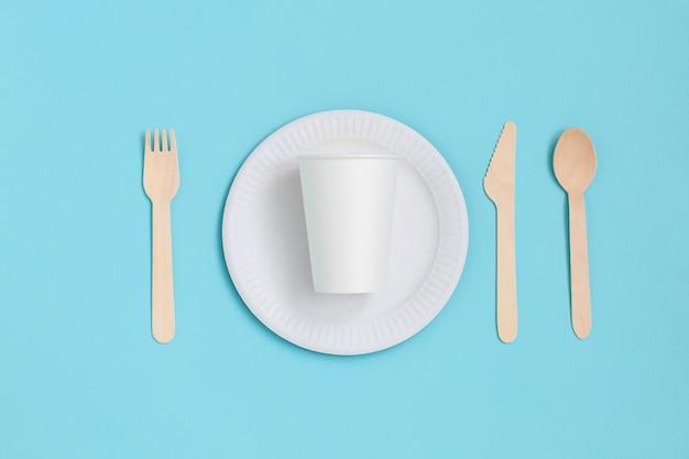 Одноразовая посуда из натуральных материалов на синем фоне. экологически чистые