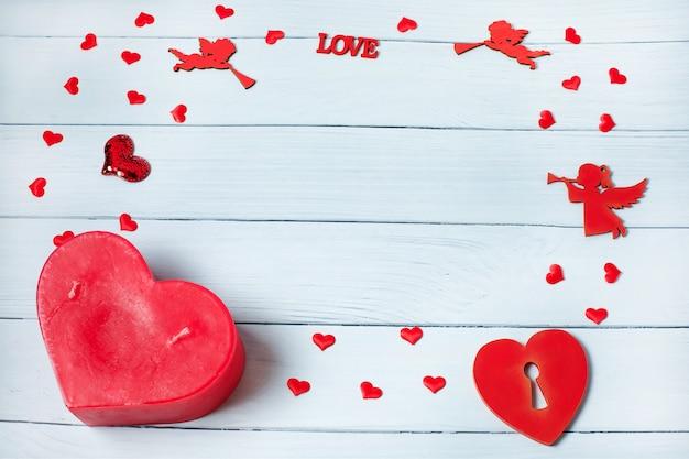 バレンタイン・デー。木製の背景にギフト、キャンドル、紙吹雪で作られたフレーム。バレンタインデーの背景。