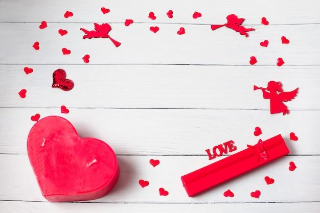 バレンタイン・デー。ギフト、キャンドル、紙吹雪、木製の背景の天使で作られたフレーム。バレンタインデーの背景。