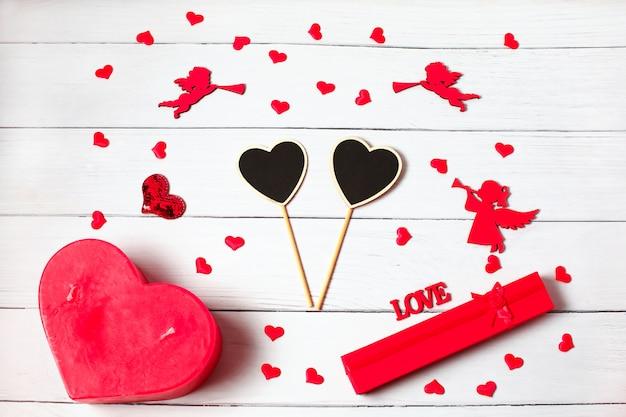 バレンタイン・デー。ギフト、キャンドル、紙吹雪、天使で作られたフレーム