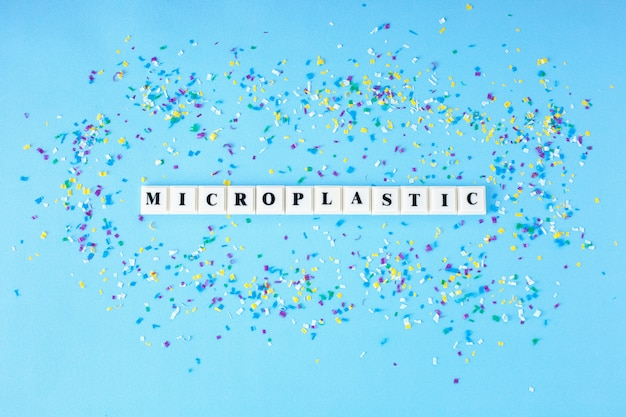 Пластиковый блок куб с словом микропластик вокруг мелких пластиковых частиц на синем фоне.