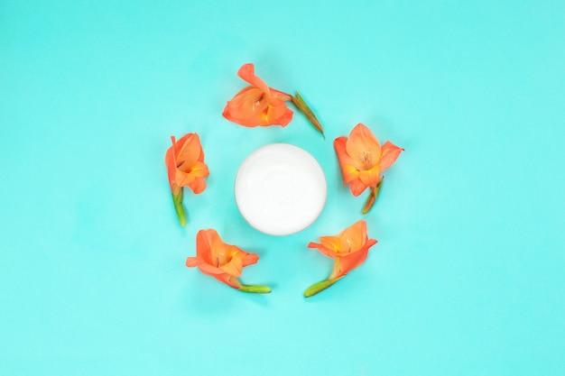 花のボディクリームが付いている化粧品のクリームの容器