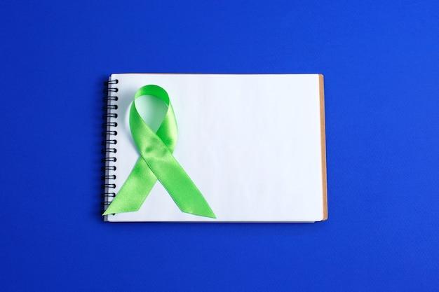 Светло-зеленая лента и открытая тетрадь. осведомленность рака печени лимфомы. концепция здравоохранения и медицины.