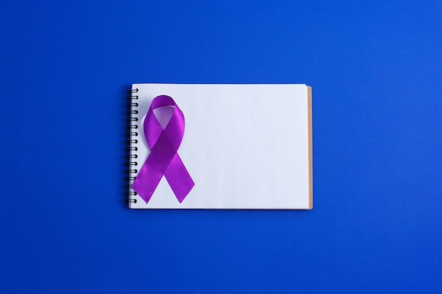 Фиолетовые ленты и открытая тетрадь, болезнь альцгеймера, рак поджелудочной железы, осведомленность об эпилепсии, осведомленность о домашнем насилии,