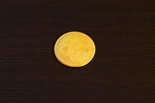 木製のテーブルに黄金のビットコイン。ビットコイン暗号通貨、ブロックチェーン技術、デジタルマネー。