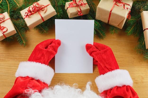 サンタクロースの手でクリスマスの手紙のクローズアップ