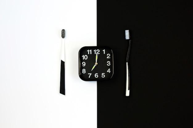 白と黒に設定された手動歯ブラシと黒の目覚まし時計。