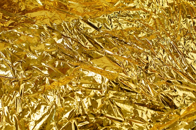 光沢のあるしわのある不均一な表面と金箔背景テクスチャ