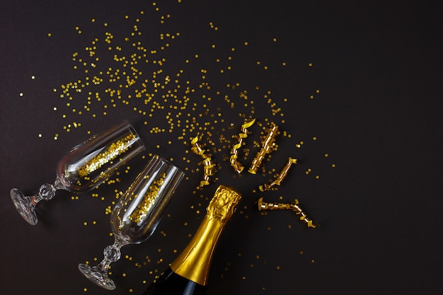 Два бокала шампанского с конфетти на черном фоне.