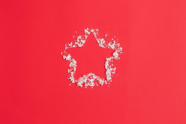 星と赤の背景に雪。クリスマスの組成物。