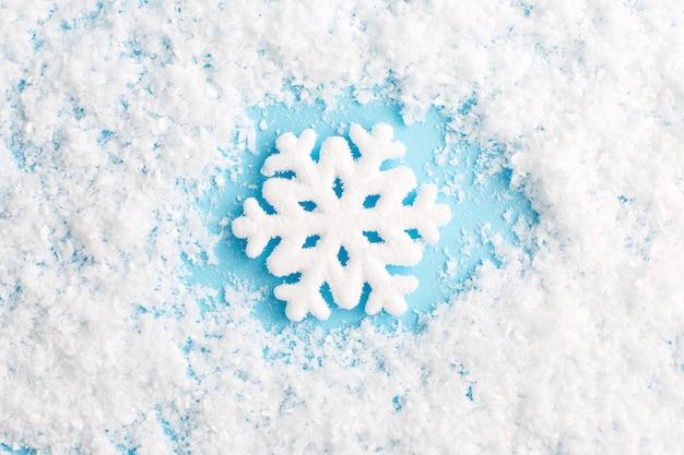 Снежинка и снег на синем фоне. рождественская композиция.