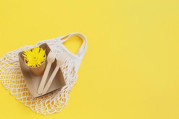 Экологичная одноразовая посуда и сетчатая текстильная сумка на желтом