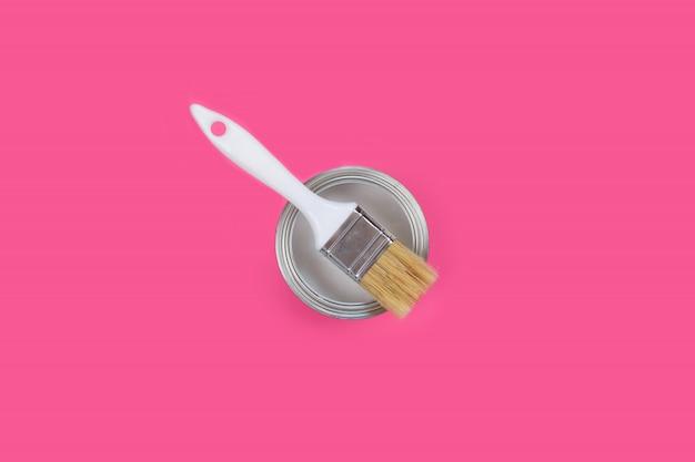 ピンクの背景に白いペンキとブラシで缶を開き、