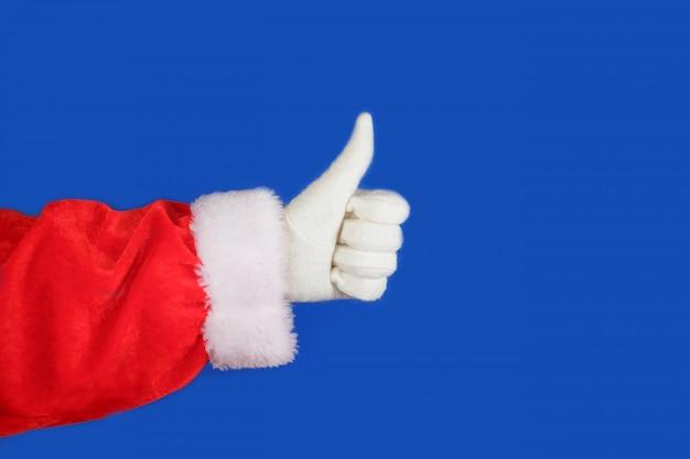 Санта-клаус рука показывает палец вверх на синем фоне