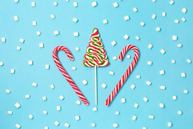 クリスマスキャンデー杖と青の背景にマシュマロとクリスマスツリー。