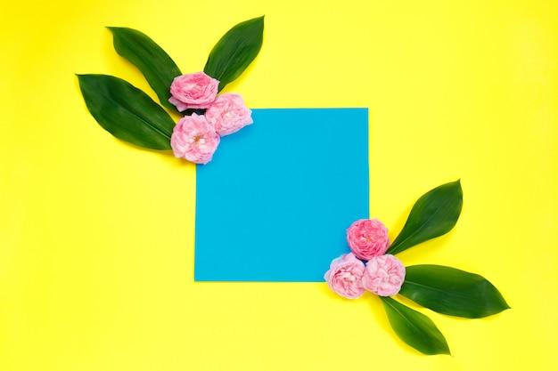 ピンクのバラの花で作られたフレームと色の背景の葉。