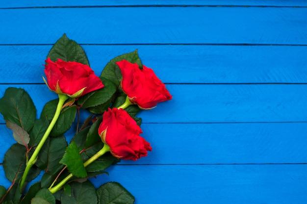 Красные розы на синий деревянный стол. день святого валентина фон.
