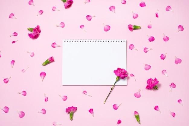 ピンクのカーネーションの花とノートブックを開くと花びら